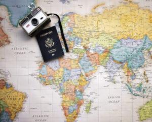 Das Foto zeigt eine Weltkarte, einen Fotoapparat und einen Reisepass. Es dient der Veranschaulichung der internationalen Ausrichtung der Escortagentur Feel in Berlin. Die Models reisen gern auch mal etwas weiter um sich zu einem Escort-Date zu treffen.